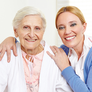 Frau umarmt Seniorin