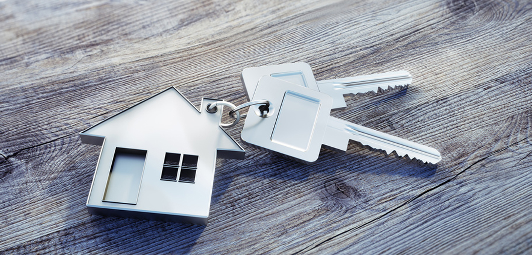 Schlüsselanhänger mit Haus auf Holzuntergrund