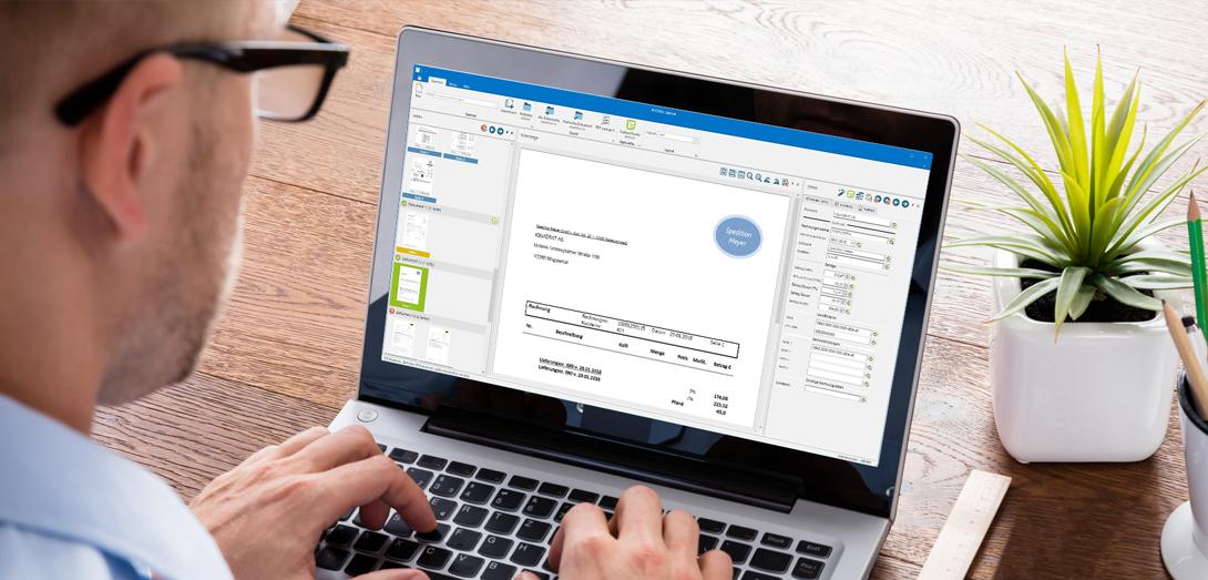 Mann gestaltet Datei an Laptop