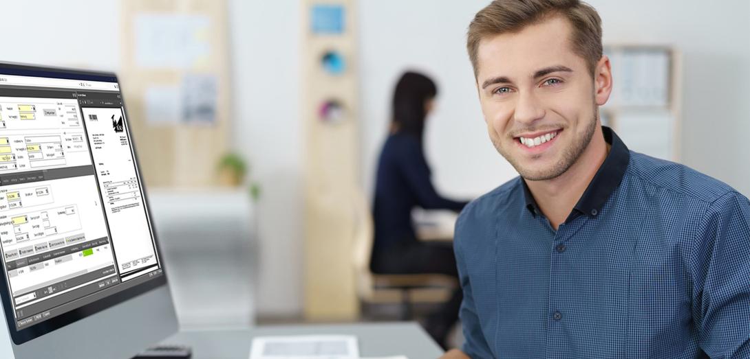 Mann sitzt neben PC und lächelt