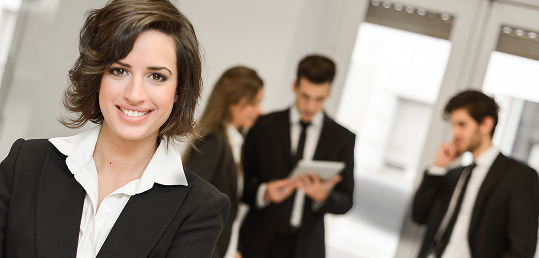 Geschäftsfrau im Kostüm mit drei Geschäftsleuten im Hintergrund