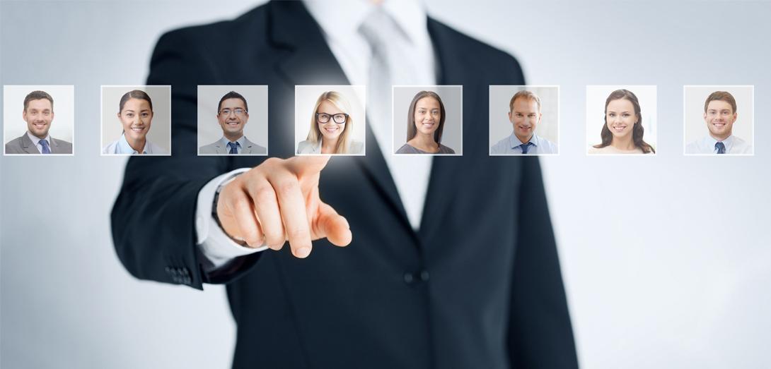 Geschäftsmann zeigt auf Bilder von verschiedenen Angestellten