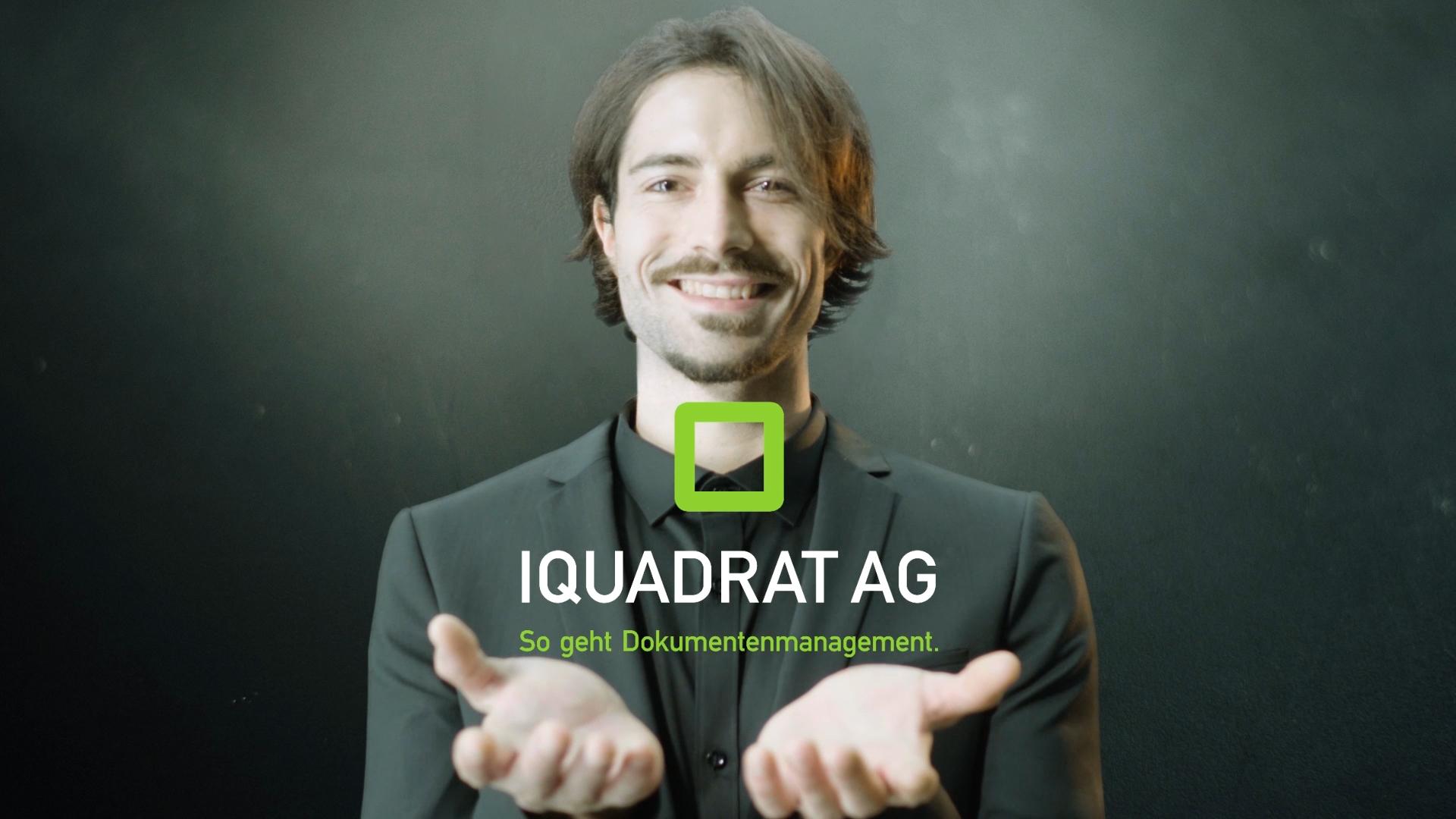 Mann präsentiert Logo der iquadrat AG