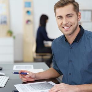 Mann an Schreibtisch mit Unterlagen
