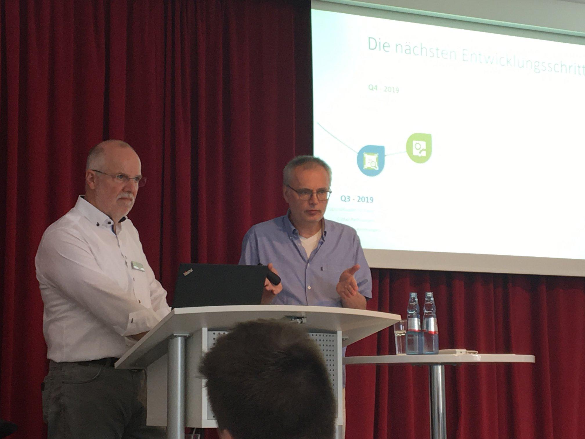 zwei Männer am Rednerpult bei einem Vortrag